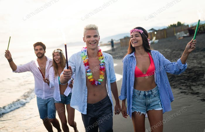 Group of happy friends having fun walking down the beach at sunset