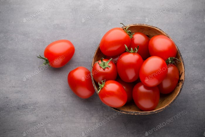 Small plum tomatoes in a wooden bowl on a gray background.