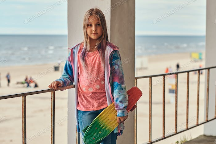 Blonde schoolgirl skater posing with a skateboard while leaning on a guardrail against sea coast.