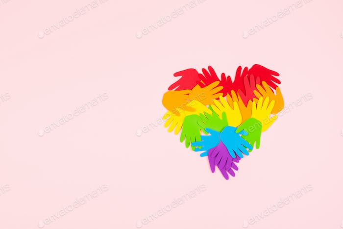 Pride month, LGBT flag symbol concept with rainbow color palm hands heart shape on pink background