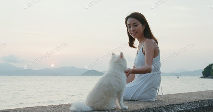 Woman enjoy sunset with her pomeranian dog at sunset
