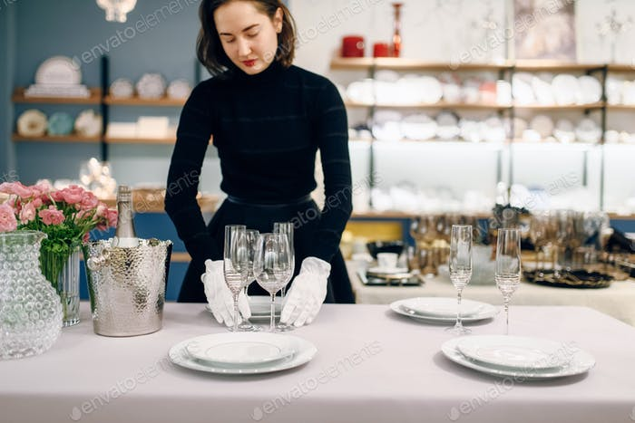 Kellnerin in Handschuhen legt das Geschirr, Tischeinstellung