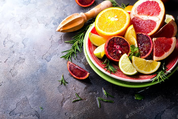 Sliced citrus fruit on the plate on stone dark background