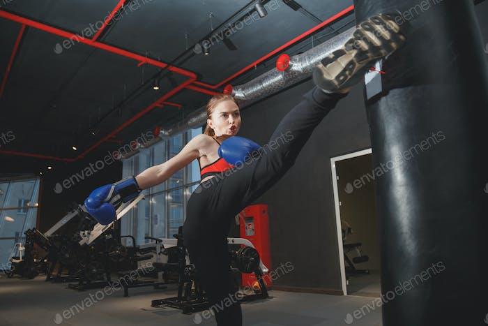Kickboxen Frau Boxsack im Fitnessstudio