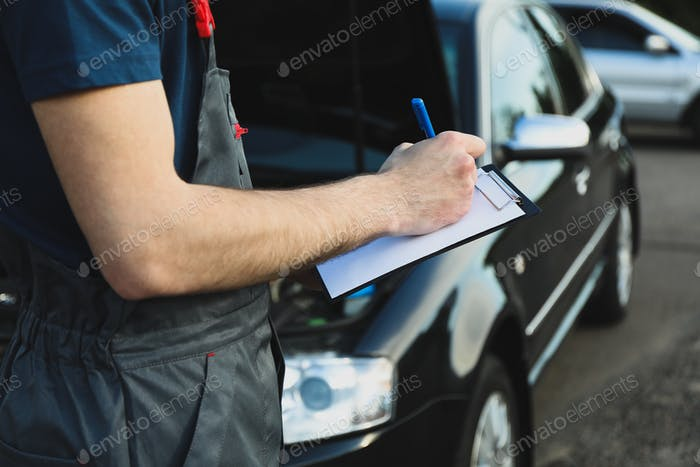 A man in overalls writes to a clipboard. Mechanic. Car inspection