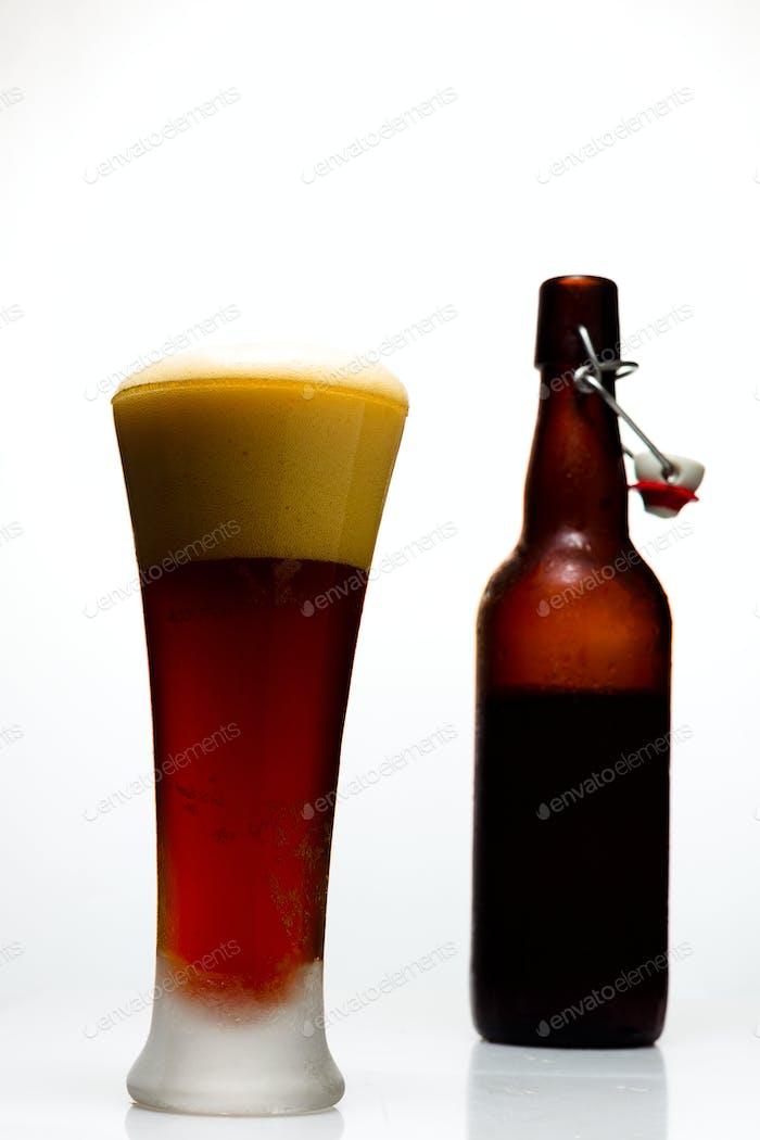 Dunkles Bier in einem Glas und eine Flasche Bier auf weißem Hintergrund