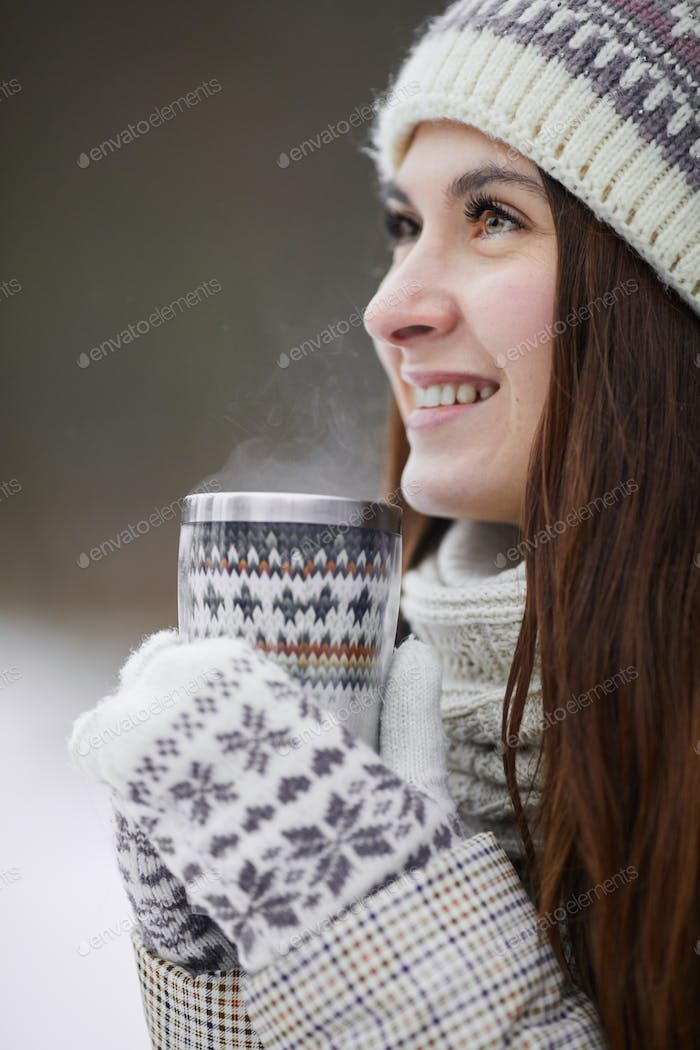 Happy Woman Drinking Hot Cocoa in Winter Park