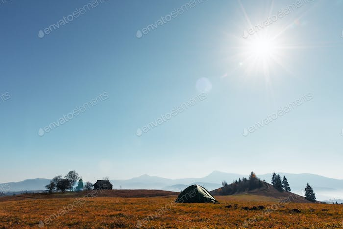 Tent against the backdrop of an incredible autumn mountains