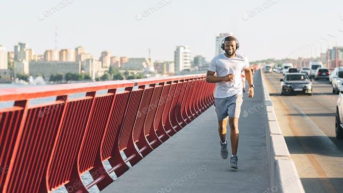 Junger Kerl läuft entlang Stadt Highway