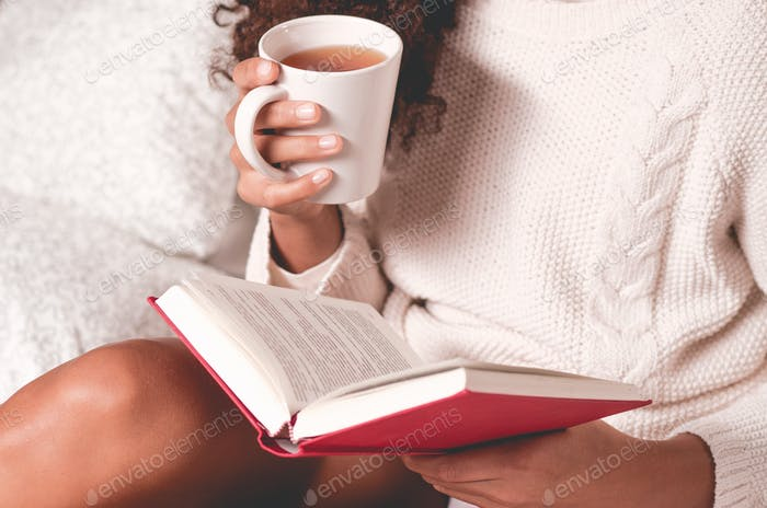Hands holding book and mug