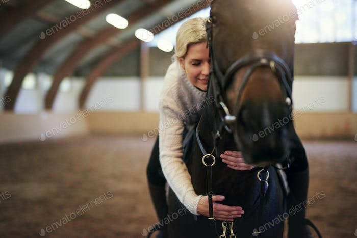 Blonde female sitting astride and hugging horse