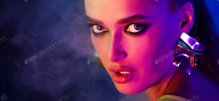 Woman with bright makeup looking at camera in neon light