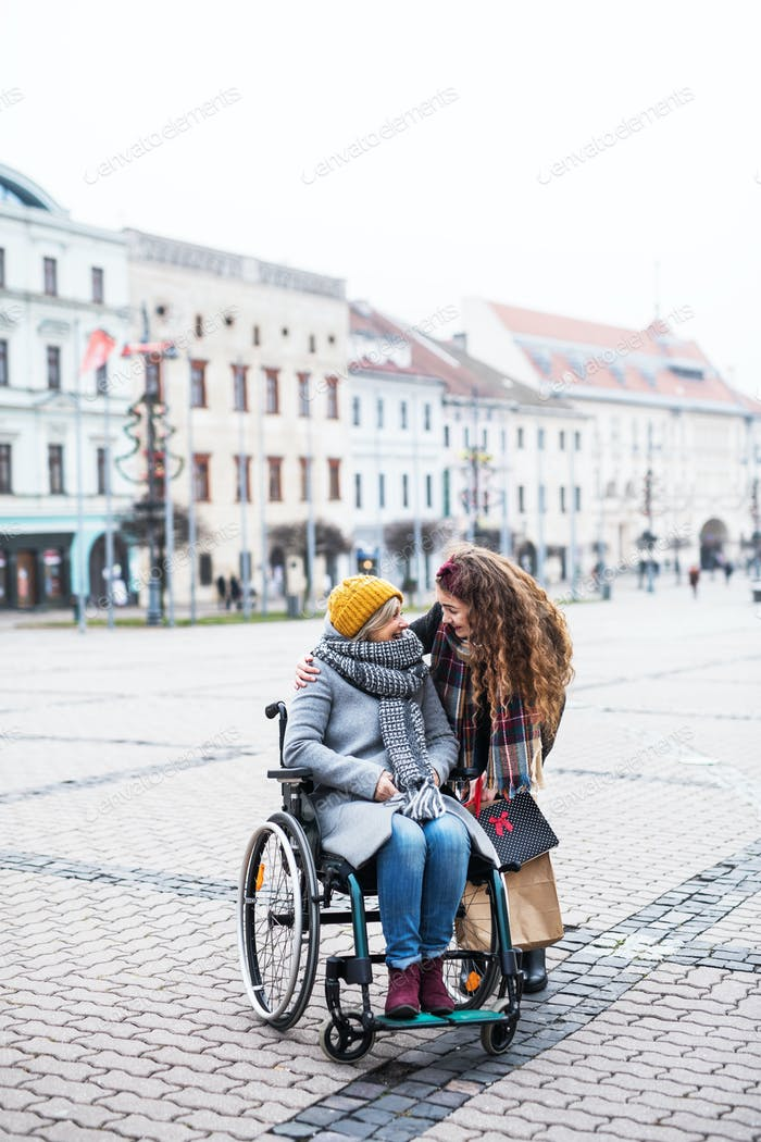 A teenager girl with disabled grandmother in wheelchair outdoors on the street in winter.