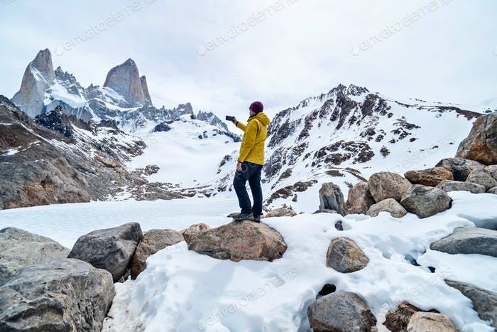 A hiker with a yellow jacket taking a photo on the base of Fitz Roy Mountain in Patagonia, Argentina