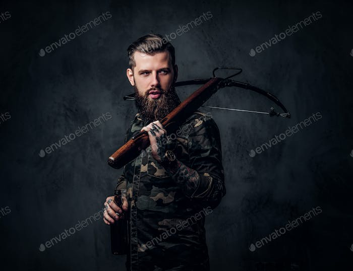 Stylish bearded hipster man in military shirt holding a craft beer and a medieval crossbow