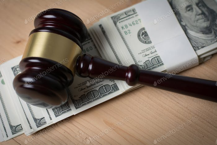 Concept of Legal court gavel on assorted cash, Close up.