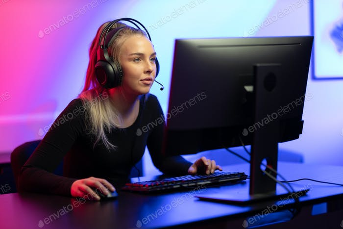 Professional E-sport Gamer Girl with Headset Playing Online Video Game on PC