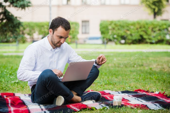 Man is working using laptop at park. Outdoor, guy look challenged and thinking
