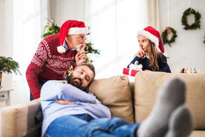 A small girl with grandfather don't want to wake up her sleeping father at Christmas time.