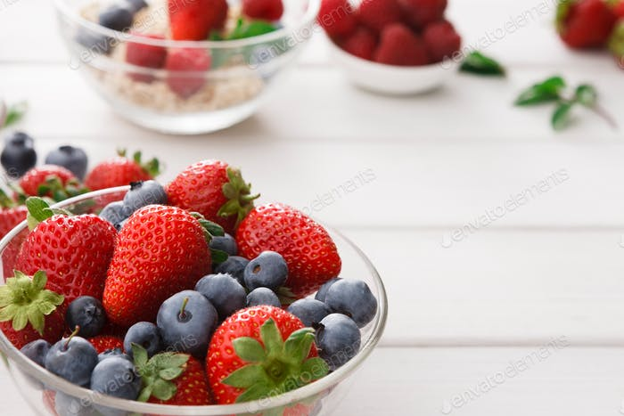 Mixed berries in glass bowls closeup, selective focus