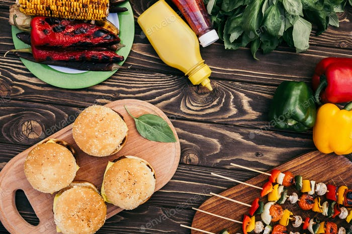 Vegetables And Mushrooms on Skewers With Burgers Cooked Outdoors on Grill
