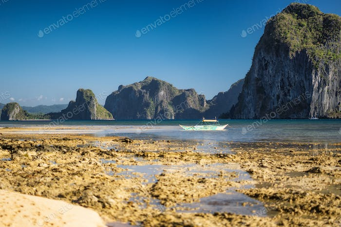Holiday vacation scene of beautiful tropical location El-Nido, Philippines. Banca boats in low tide