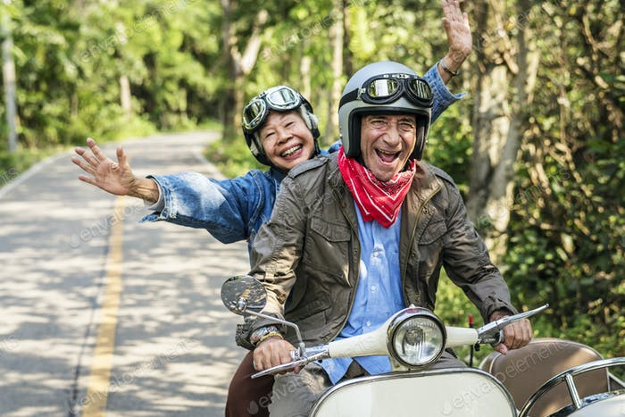 Senior couple riding a classic scooter