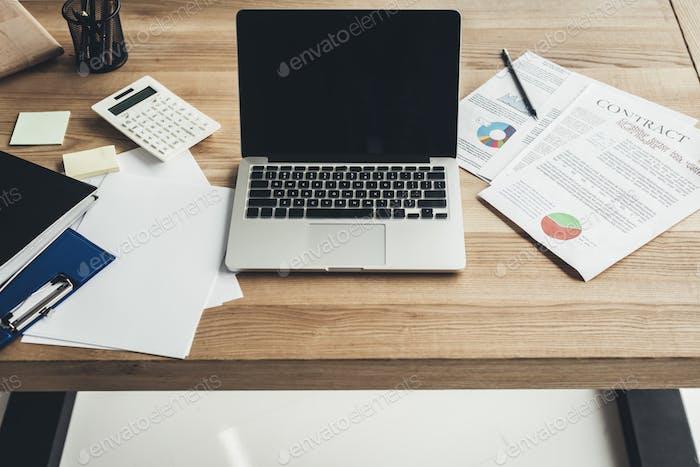 lugar de trabajo moderno con computadora portátil y documentos en el escritorio