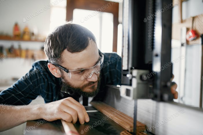 Professional carpenter working with sawing machine