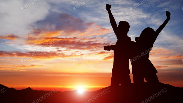 Silhouette of couple celebrating success against colorful sky