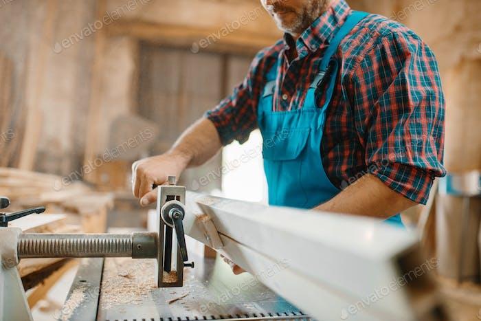 Carpenter works on plane machine, woodworking