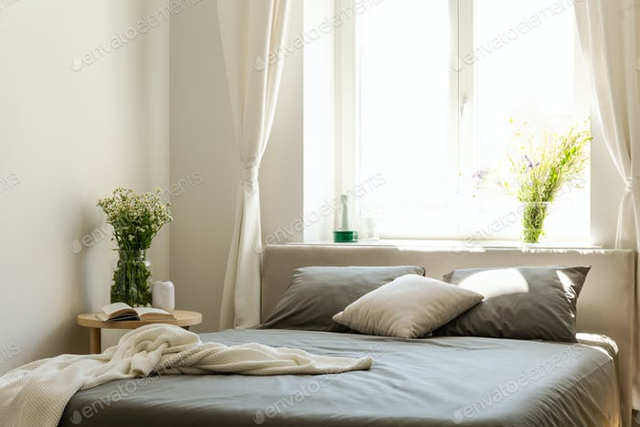 Blanket and pillows on grey bed in bright bedroom interior with