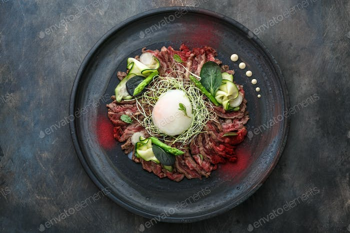 Beef Tataki with onsen egg, zucchini and mayo, restauran meal, copy space.