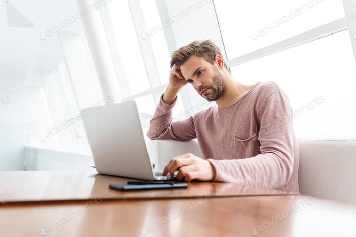Image of young bearded man using laptop computer in cafe indoors