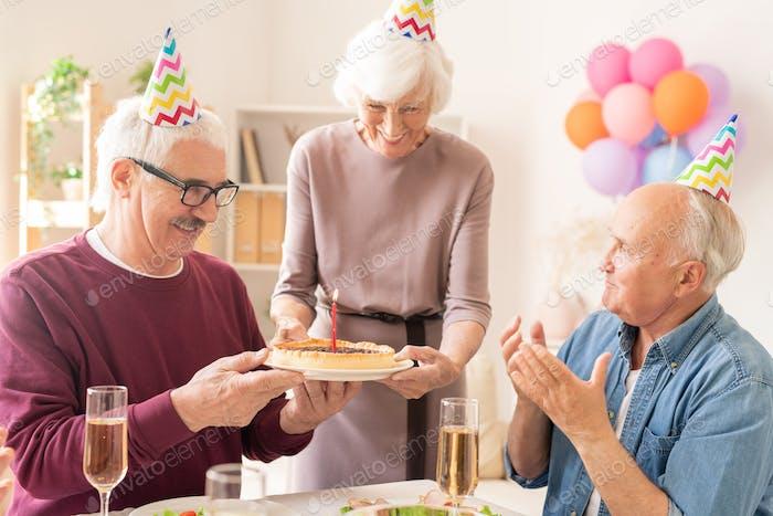 Happy grandmother bringing sweet homemade pie