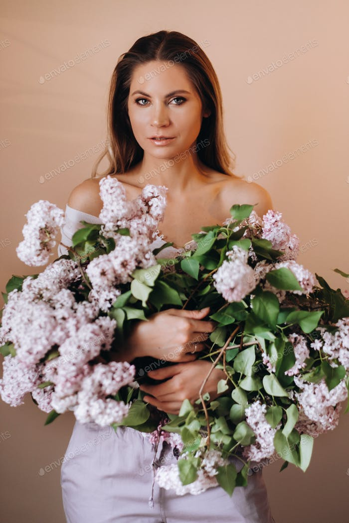 Beautiful girl with lilac flowers in her hands. A girl with lilac flowers in the spring at home. A