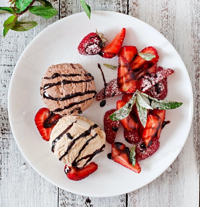 Ice cream with strawberries and chocolate on a white plate