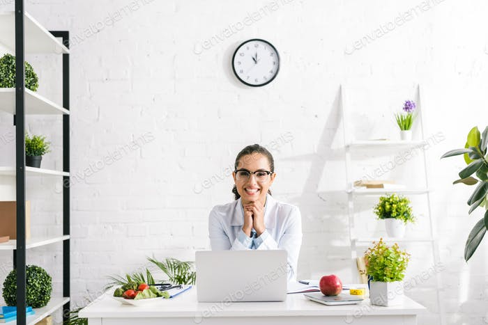 cheerful nutritionist in white coat near vegetables and laptop