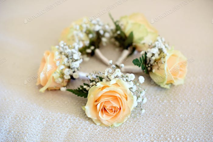 Five peach rose corsages lying in circle