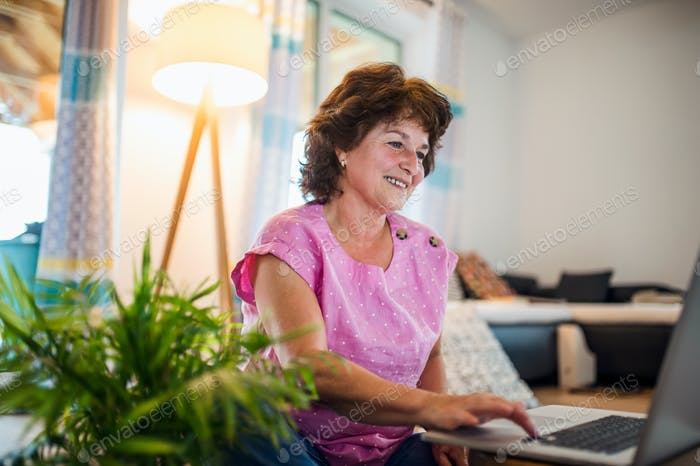 Mujer mayor con portátil sentado en casa, trabajando