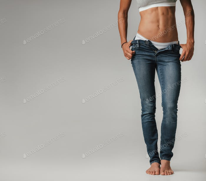 Sexy toned young woman posing with unzipped jeans