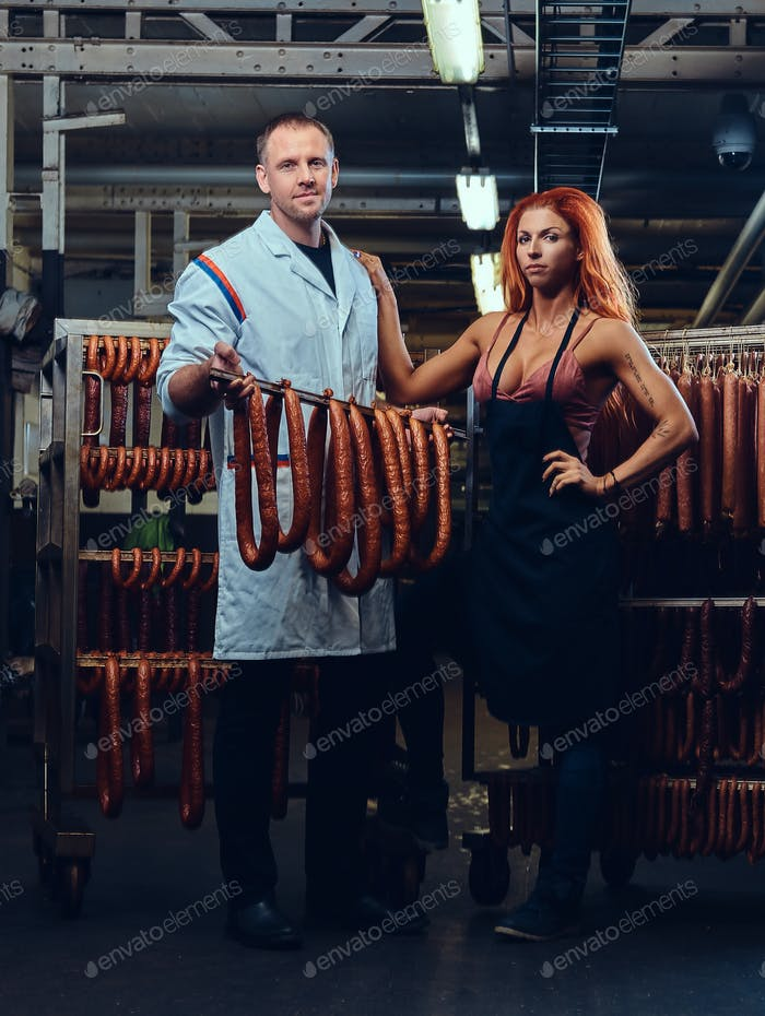 A chef and his female helper in a sausage storage.