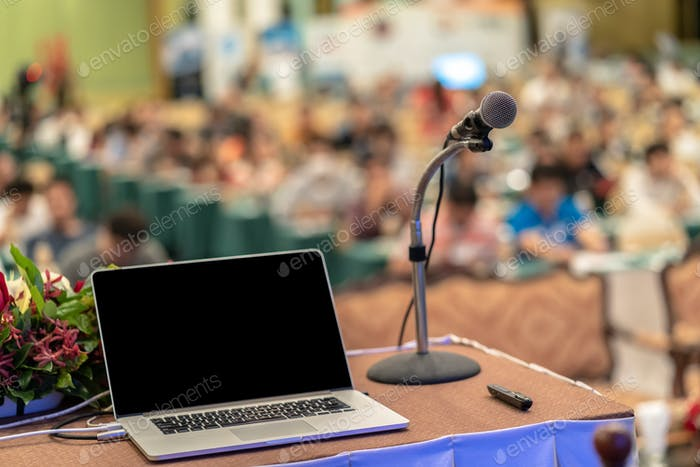 Microphone and tecgnology laptopn on the table over the Abstract blurred photo of conference hall