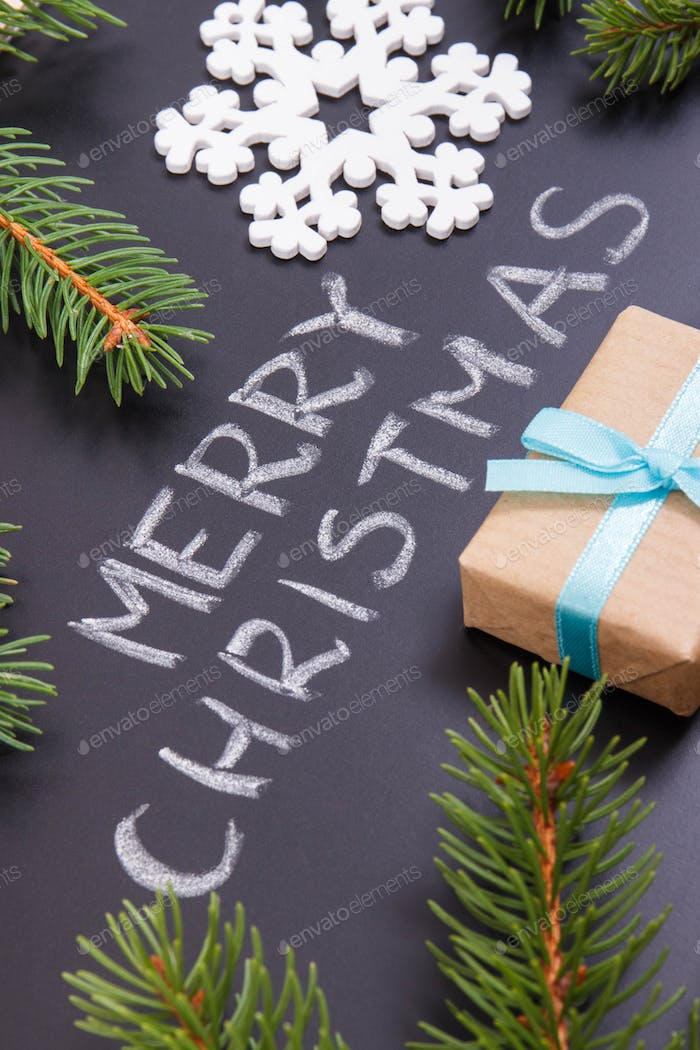 Inscription Merry Christmas, wrapped gift with ribbon and spruce branches