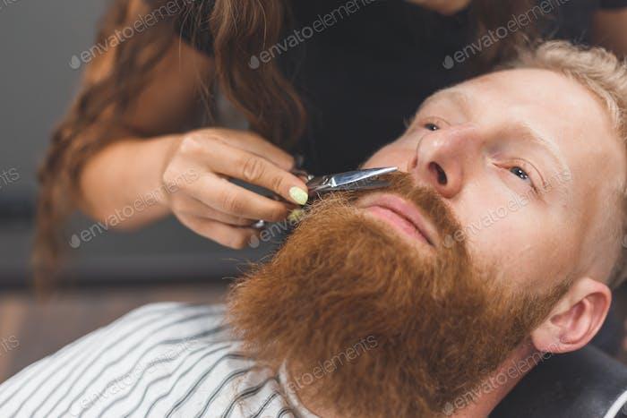 Ein Mann in einem Friseurladen. Frau Friseur Clipping Schnurrbart. Barbier Frau in Maske.