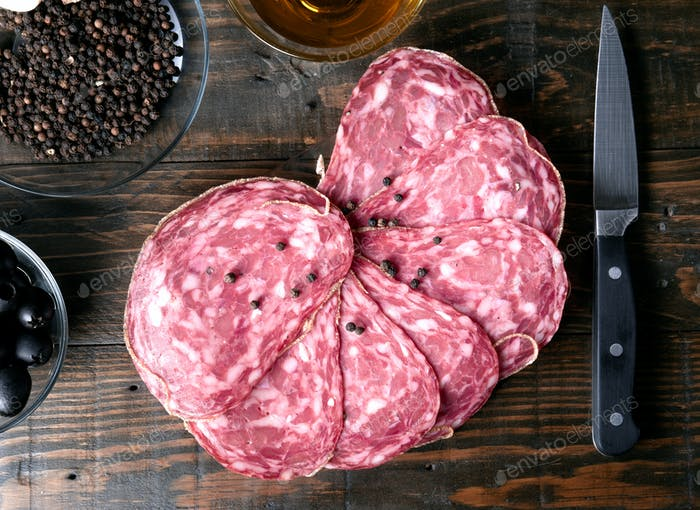 overhead shot slices of Iberian sausage on wooden board