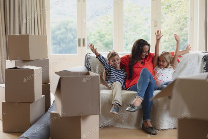 Front view of Caucasian mother and children having fun in living room at home
