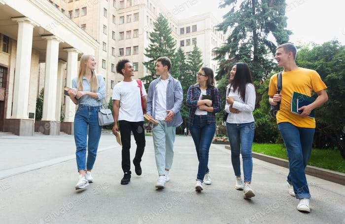 Happy students walking outside the university building