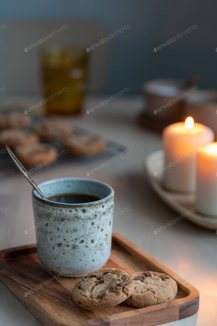 Cozy evening, mug of drink, holiday decorations, candles lights. Vertical still life twilight