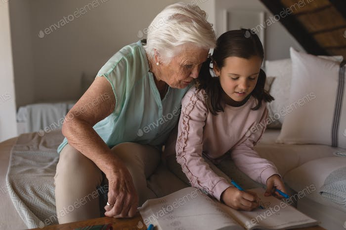 Front view of a grandmother helping her granddaughter with homework in living room at home